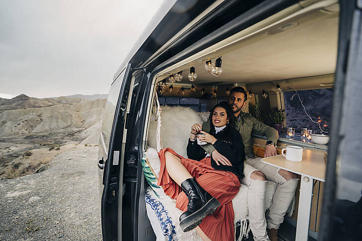 Young couple inside camper van in desert landscape, Almeria, Andalusia, Spain